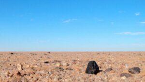 Fragmento negro del meteorito Almahata Sitta encontrado en el desierto de Nubia al norte de Sudán