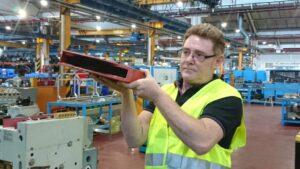 Trabajador sostiene una pieza que contenía amianto.