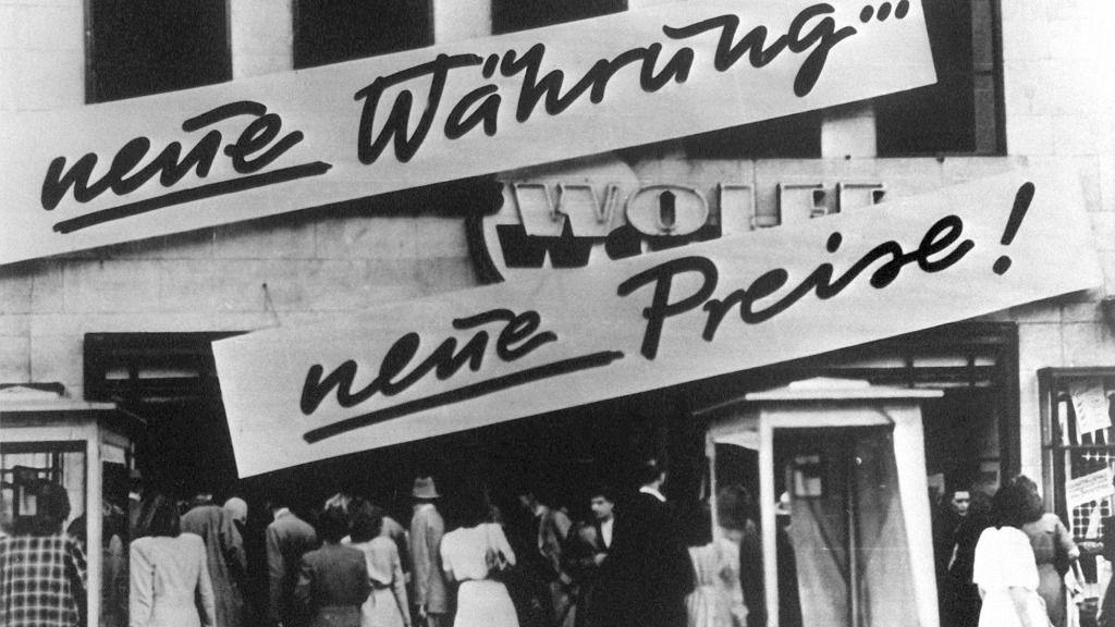 """Clientes se agolpan frente a un negocio que después de la reforma monetaria en Alemania. En la fachada se lee """"¡Nueva moneda... nuevos precios!"""". En 1948 se introdujo el marco alemán"""
