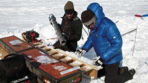 Mike MacFerrin (izquierda) y Horst Machguth (derecha) analizan muestras de núcleos de hielo perforadas en la capa de hielo de Groenlandia en 2012