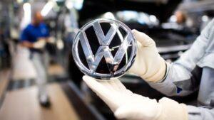 Trabajador de Volkswagen muestra el logo de la automotriz alemana