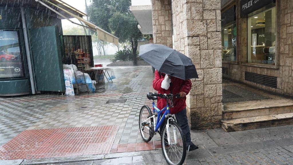 Un ciclista con un pagaguas resguardándose de la lluvia y el viento