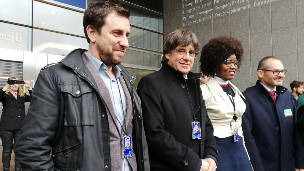 El expresidente catalán, Carles Puigdemont (centro), y su exconsejero de Sanidad, Toni Comín (izquierda) posan con sus credenciales de eurodiputados, el 20 de diciembre en Bruselas