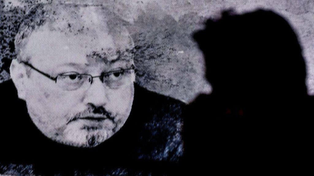 Un hombre pasa frente a una pantalla con la imagen de Jamal Khashoggi durante un acto de recuerdo del periodista saudí, realizado el 11 de noviembre de 2018 en Estambul