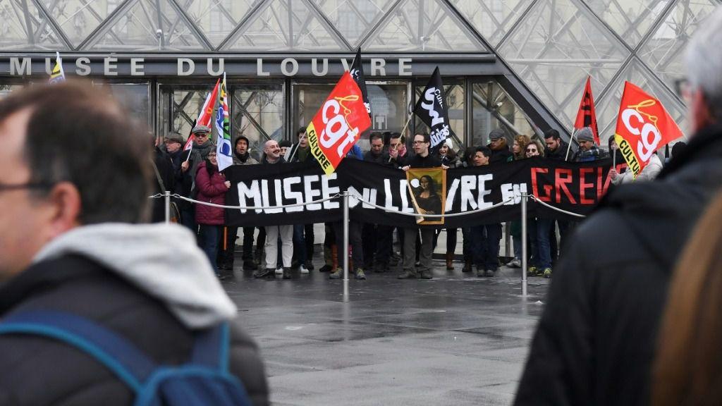 """""""Museo del Louvre en huelga"""", se lee en la pancarta de unos manifestantes el 17 de enero de 2020 en la pirámide de acceso parisina diseñada por Ieoh Ming Pei"""