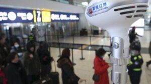 Personal del Aeropuerto Internacional de Tianhe en Wuhan (China) toma la temperatura a pasajeros