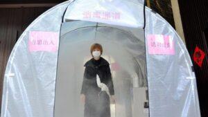 Una mujer camina a través de un canal de desinfección situado en la ciudad de Hefei, en el oeste de China
