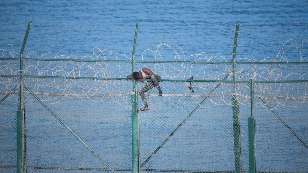 En la imagen, uno de los 153 migrantes, que han entrado en Ceuta saltando su doble valla en la primera incursión en grupo en un año; se aferra a las concertinas