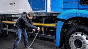 Un conductor cargando su camión eléctrico