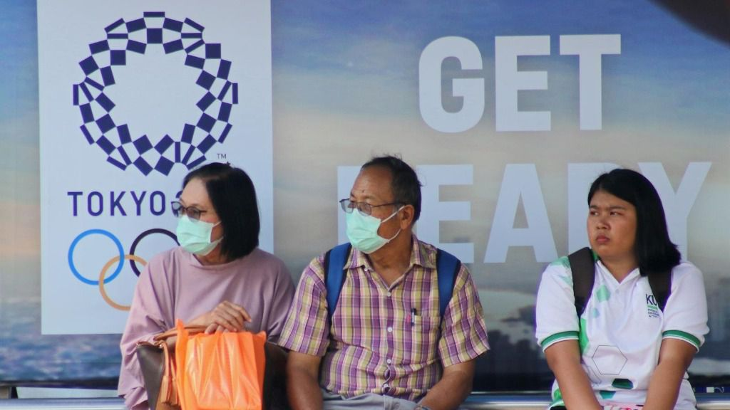 Ciudadanos tailandeses ante un cartel de los Juegos Olímpicos de Tokio en Bangkok