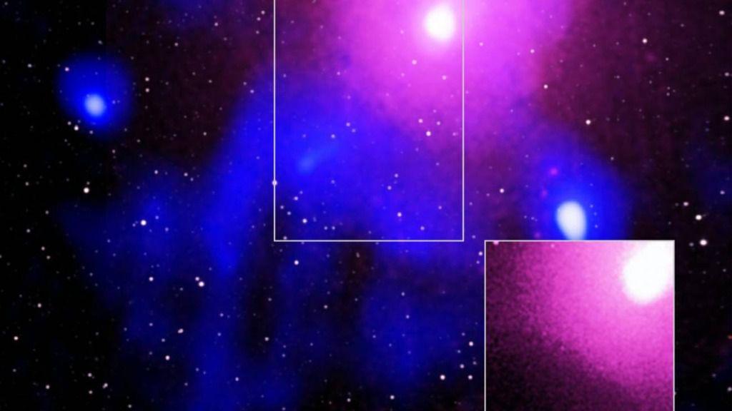 a colosal explosión ocurrió en el cúmulo de galaxias Ofiuco, localizada a unos 390 millones de años luz de la Tierra. Imagen obtenida con los datos de los telescopios XMM y GMRT y del sondeo galáctico 2MASS. La zona central recuadrada se muestra en otro c