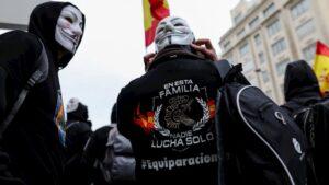 Manifestantes con máscaras de Anonymous y una camiseta en la que reza 'en esta familia nadie lucha solo #equiparación' frente a las puertas del Congreso de los Diputados.