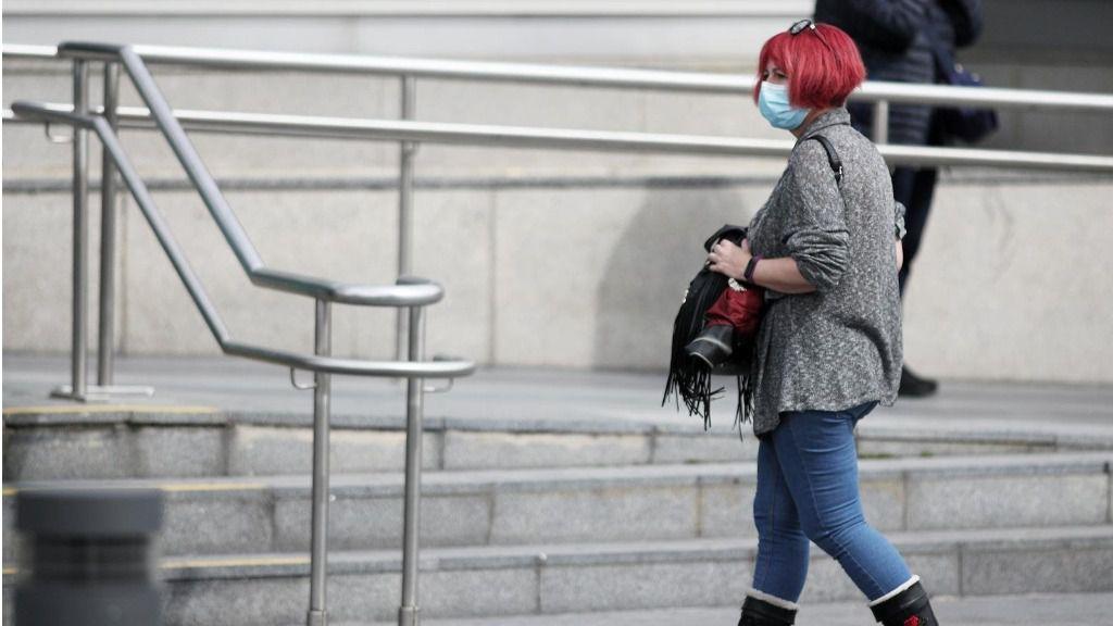 Una mujer protegida con mascarilla a las afueras del Hospital de la Paz