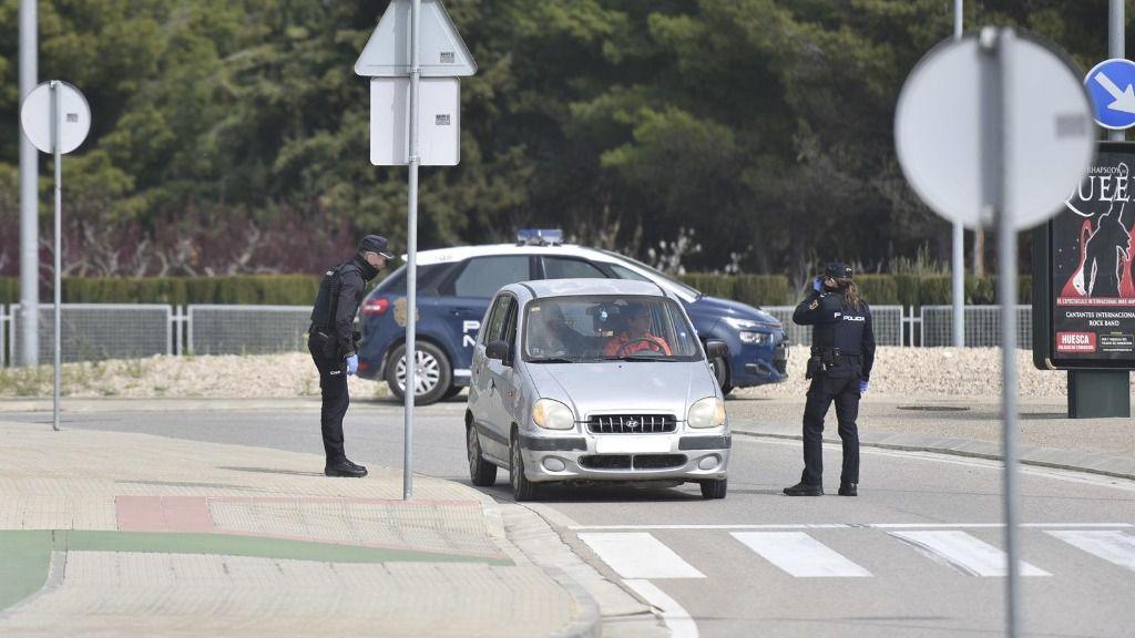 Dos policias nacionales paran a un coche estacionado durante el cuarto día laboral en el estado de alarma en el país por el coronavirus