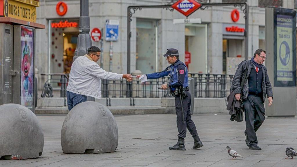 Un policía municipal de Madrid pone una multa a un viandante por no respetar la cuarentena en Madrid