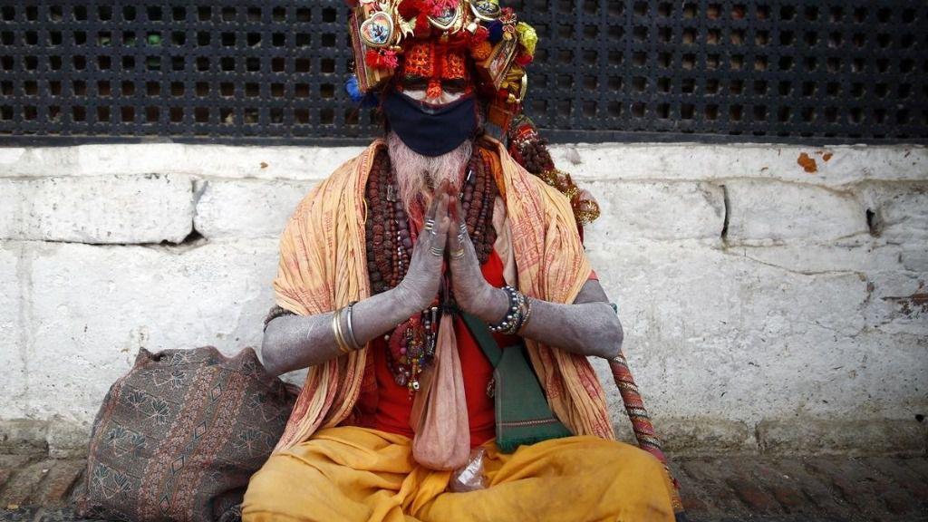 Un monje hindú con mascarilla