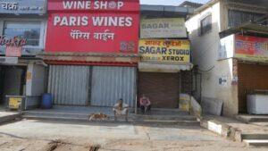 Dos ciudadanos sentados a las puertas de una tienda de vinos en Bombay