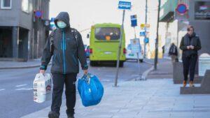 Un hombre camina por las calles de Oslo, Noruega, cubriéndose la boca con una mascarilla