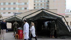 Personal sanitario pasa junto a militares en las inmediaciones del Hospital Gregorio Marañón