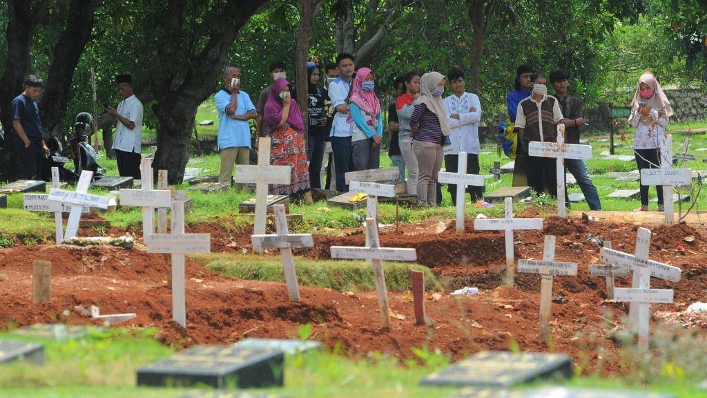 Personas con mascarilla por el coronavirus en un cementerio de Yakarta