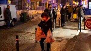 Un mujer ataviada con una mascarilla sale de una tienda de comestibles después de que el Gobierno decretara un toque de queda de 48 horas para el pasado fin de semana y que provocó largas colas en colmados y locales de alimentación