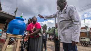 Un médico toma la temperatura mientras una mujer se lava las manos en Nairobi