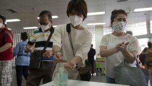 Un grupo de personas se desinfectan las manos con gel antes de entrar a un supermercado en Bangkok, Tailandia
