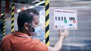 Un empleado de Ford colocando un cartel que pide distanciamiento entre los trabajadores para evitar contagios.
