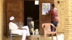 Sudaneses frente a un cartel informativo sobre las medidas de protección ante la pandemia de coronavirus
