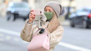 Una mujer con mascarilla haciendo una foto con su smartphone en Londres