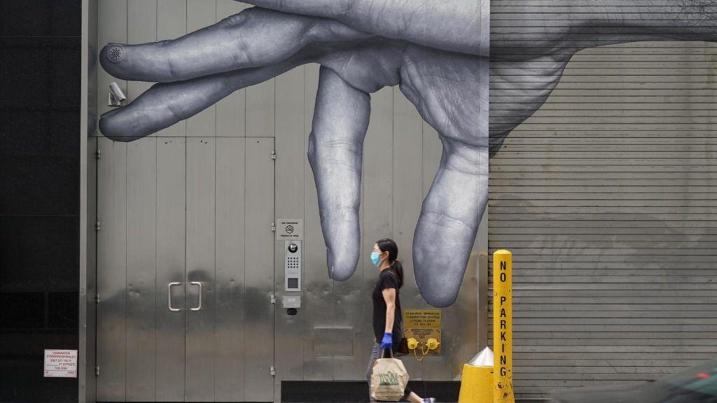 Una mujer con mascarilla paseando ante un mural en Nueva York coronavirus