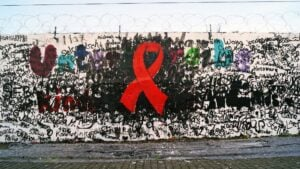 Crespón rojo pintando en una pared, un gesto simbólico para reivindicar el Día Mundial de la lucha contra el VIH sida