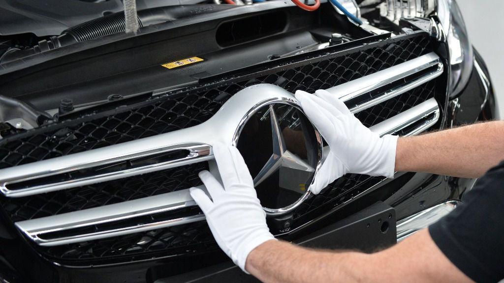 Un empleado de Mercedes-Benz monta una estrella en un coche de la Clase C en una planta de producción de Daimler en Bremen, Alemania
