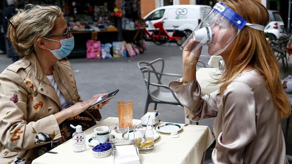 Dos personas sentadas en una terraza en Roma italia coronavirus