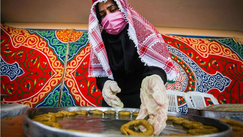 Una mujer palestina con mascarilla en Gaza preparando dulces tradicionales coronavirus