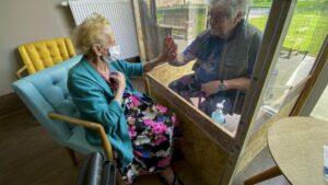 Una mujer en una residencia de ancianos recibe una visita en Bélgica coronavirus