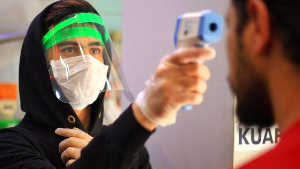 Un dependiente de una tienda en Turquía toma la temperatura a un cliente.