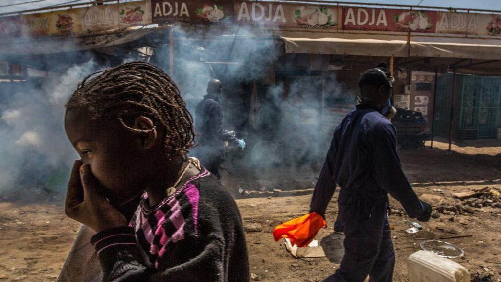 Varias personas caminan por un mercado de Dakar, Senegal, mientras un trabajador desinfecta sus calles