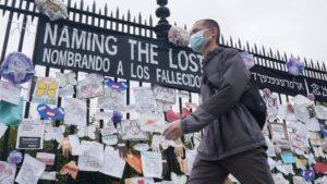 Un hombre pasa ante una verja en Nueva York con mensajes en memoria de los fallecidos por la pandemia del coronavirus