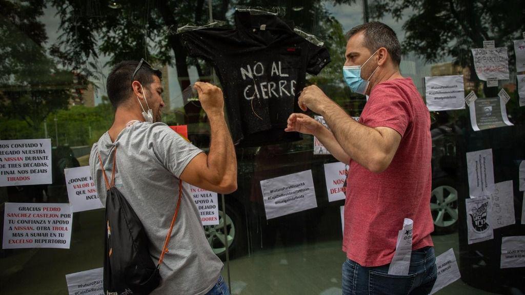 Varios trabajadores de Nissan cuelgan carteles como signo de protesta