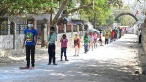 Niños con mascarilla por el coronavirus hacen cola en India para conseguir el menú escolar