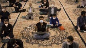Hombres rezando con mascarilla en una mezquita en Teherán