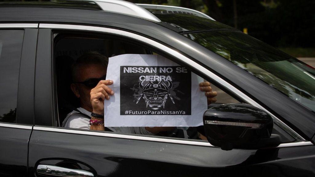 Una trabajadora de Nissan Motor Ibérica, en la Zona Franca de Barcelona, sujeta un papel desde su coche en el que se lee 'Nissan no se cierra'