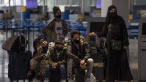 Migrantes y refugiados esperan para embarcar en Atenas rumbo a Londres