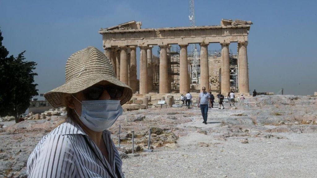Una mujer con mascarilla frente al Partenón de Atenas