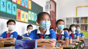 Niños chinos acuden a clase en Pekín china coronavirus