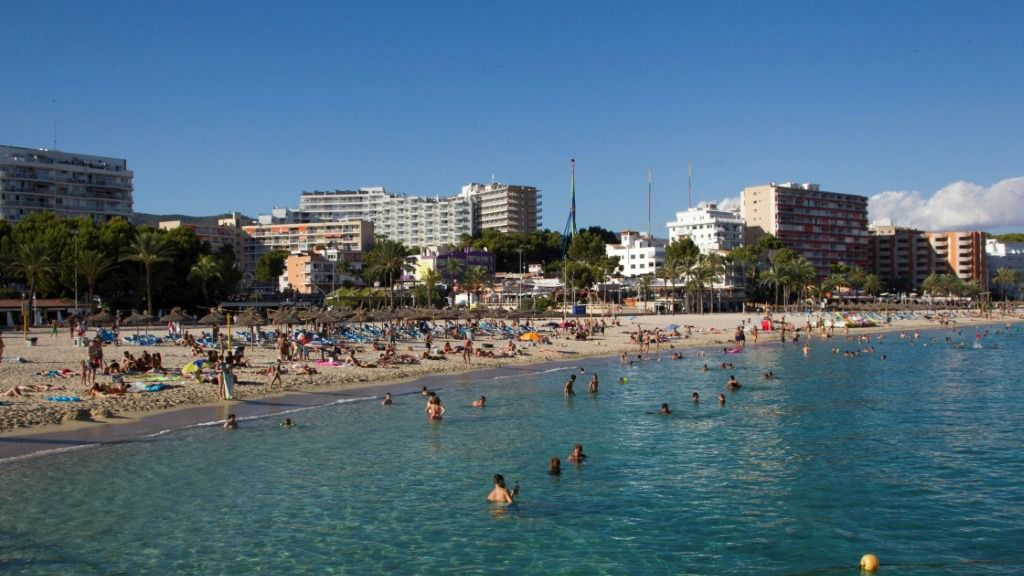 Unos turistas se bañan en la playa de Magaluf, en Calvià, en la isla española de Mallorca