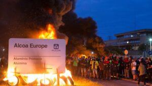 Manifestantes durante una concentración nocturna convocada por el comité de Alcoa San Cibrao, en el entorno de la fábrica de San Cibrao, queman el cartel de la multinacional en Lugo, Galicia (España), a 30 de junio. La manifestación, es una de las tantas
