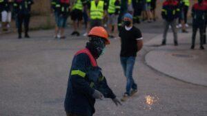 Un manifestante tira un petardo durante una concentración nocturna convocada por el comité de Alcoa San Cibrao, en el entorno de la fábrica de San Cibrao