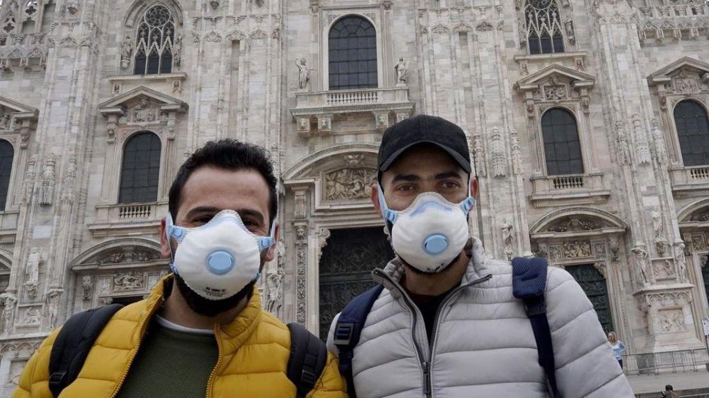 Turistas con mascarilla frente a la catedral de Milán